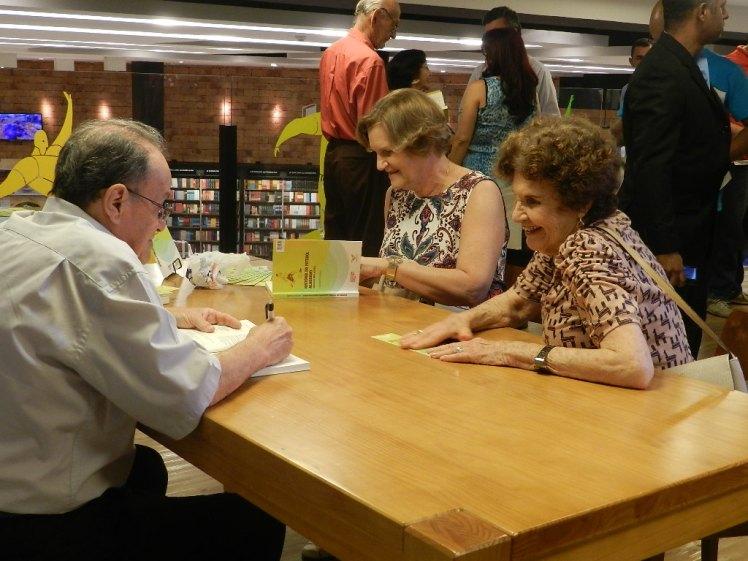 Lauthenay escrevendo dedicatórias em seu livro para as leitoras